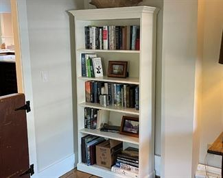 PAIR WHITE PAINTED BOOKSHELVES | Beautiful contemporary custom bookshelves with crown moldings, painted white; each h. 71 x 36 x 14 in.; two shelves being sold together, one in the house the other in a storage room