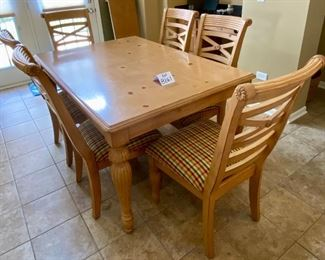 """Lot 8261. $350.00. Knotty Pine Solid Wood Kitchen Table.  It's a great workhorse of a table and includes 1 leaf and 6 chairs (one chair needs the seat pad to be resecured to the base). Light colored wood with column-ish style legs, the chair seats are a nice plaid with red, gold, cream seat pads. Normal usage wear.61""""l x 42""""w x 31""""t, 1 18"""" leaf, 6 chairs: 21""""w x 27"""" d x 41""""t to back"""