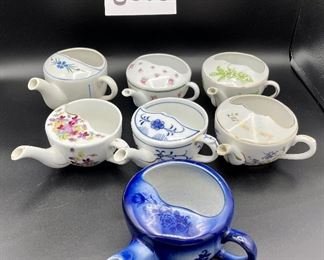 """Lot 8255.  $70.00. Lot of 7 side- handled infant/hospital/invalid feeders. All have a design and/or are colored in some way. 1) signed Vienna, Austria Edelweiss floral design,""""Fur Genesung"""", which translates to """"for recovery"""", 2) Cobalt blue color with floral images, 3) Purple violets, Vienna, Austria, 4) Pink rosebud design made in Victoria, Austria, 5) White with blue flower from London Covent Garden, 6) Lily of the Vally, marked #357, and 7) blue floral design embellishes the entire feeder cup."""
