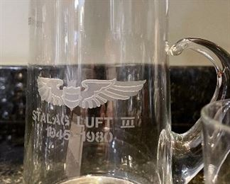 """Lot 8323. $60.00 """"Off we go into the Wild Blue Yonder...."""" a set of 8 silver rimmed Air Force Academy low-ball glasses and Stalag Luft pitcher with glass stirrer and a single low-ball glass."""