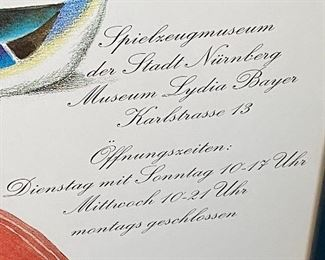 Lot 8334. $40.00 Set of 2 colorful Spielzeug Museum posters, framed in a blue frame.