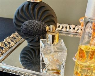 Lot 8360.  $90.00 Perfume Lot includes: Mirrored dresser/vanity tray and opened perfume bottles including White Linen by Estee Lauder, Tresor by Lancome,  a black perfume bottle and two bottles with atomizers.
