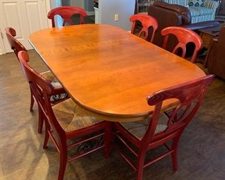 """Lot 8238. $300.00  Beautiful Cherry Wood Dining Table with Wrought Iron Base and 6 Pottery Barn Napoleon Dining Chairs with Rush Seats in Red (.Very Rare). Table 42"""" W x 68"""" L w/o Leaves, 2 Leaves 14"""" W"""