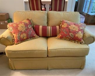 Two CR Laine love seats with two floral pillows each