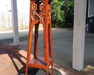 $185 - art nouveau style carved pedestal or plant stand w/ square top tier connected to a low second shelf by tapered legs. The apron depicts two flowers on each side, their stems crossing and leaves curling together.