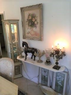 This wall table has a candelabra-style lamp, a horse statuette, and more artwork above and below.  A small display cabinet is in the left side of the frame.