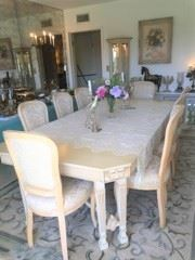 The formal dining table with eight matching chairs.