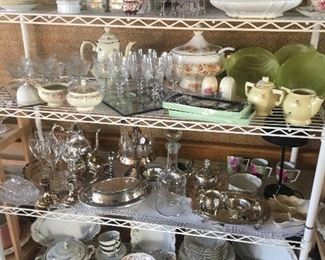 Many serving pieces, stemware, teapots and cups, vases