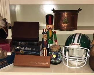This lot contains a variety of books, some statues, Trivial Pursuit game with boomer pack, a Spartans football helmet, and a jar marbles. One nutcracker is missing a foot. https://ctbids.com/#!/description/share/949826