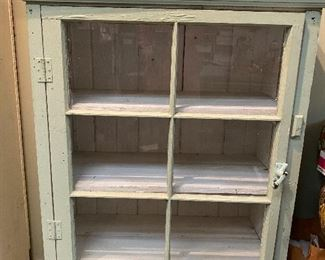 Several farmhouse style cabinets with chalky paint and glass doors
