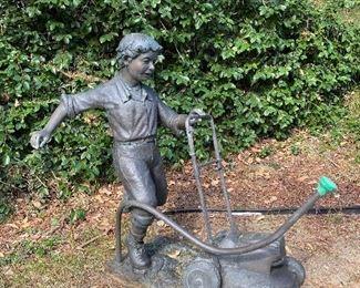 Bronze boy cutting grass