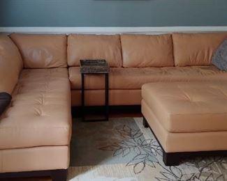 Tan leather sectional sofa and ottoman