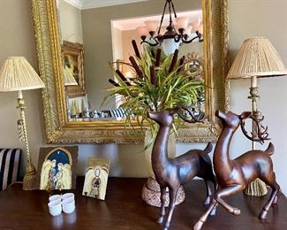 Large rectangular beveled mirror, tall lamps, small paintings, cat tails in vase, reindeer pair.