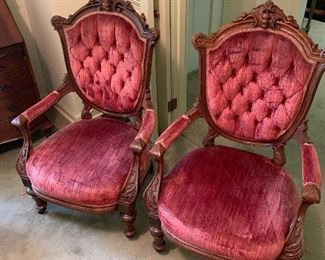 Victorian style matching chairs with velvet material seating.