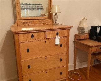 The chest of drawers with attached mirror.
