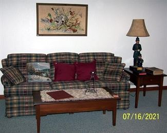 Plaid sofa, coffee table, end table, Constable lamp and liquor bottle, framed stitched piece