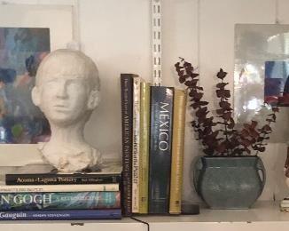 Book shelf with various art books, 2 Original Art Pieces, Antique Brass Candlestick, Art Glas Ball Bottle Vase, Bust Sculpture by Jane Paden, Vintage Roseville Vase, Antique MacBeth Figurineand a large Brass Pan,