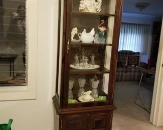 Tall Narrow China Cabinet Full of Ceramic and Glass Items