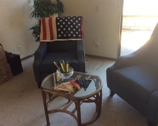Blue upholstered chairs, flag, rattan table