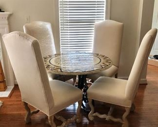 Room view -- Inlaid marble table with metal base and four upholstered chairs.