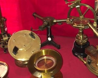 Collection includes antique compasses, galvanometers, spectroscopes, Leyden jars etc. Heliochronometer or sun dial in background left.