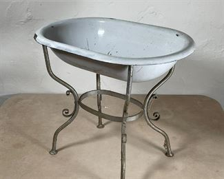 ENAMELED PORCELAIN BIRD BATH | White bird bath on a quadruped base with applied scrollwork; overall h. 16-1/4 x 19-1/2 in. [with chip to one edge]