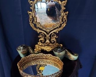 Gold gilt dresser mirror, mirrored tray and Roseville candleholders.