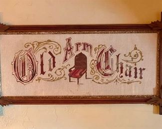 """Punched paper embroidery of """"Old Arm Chair"""" in red, framed in Victorian carved oak leaf corners criss-cross frame"""