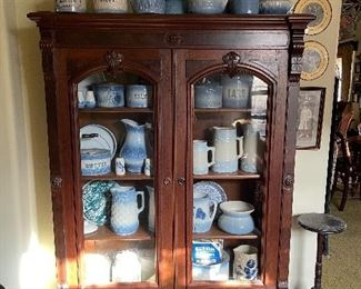 Large collection of blue salt glaze stone ware in an antique walnut cupboard