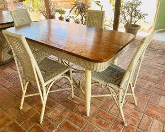 Tiger oak and wicker dining table with four high back white wicker chairs.