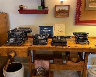 Corona and Underwood typewriters, primitive work bench, crocks, wooden storage boxes.  Rural scene framed canvas.