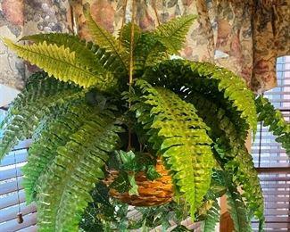 Faux fern plant in wicker hanging basket