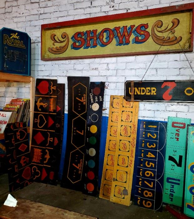 """Carnival/circus vintage signs. Huge, metal """"SHOWS"""" sign, wired for lights. Wooden over/under signs. Other various sets of wooden carnival game signs."""