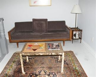 mid-century sofa, industrial iron desk, faux bois table/lamp, Persian carpet.
