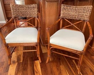 Cane chairs with woven backs and linen fabric seats.
