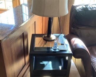 """Black side table with shelf. Measure 19.5"""" square and 25"""" high.  Presale $85 after Sept. 9.  Lamp measures 26"""" h"""