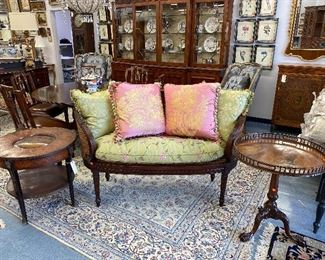 Caned back salon settee with silk cushion, Silk pillows, antique round occasional table, antique tilt top table.