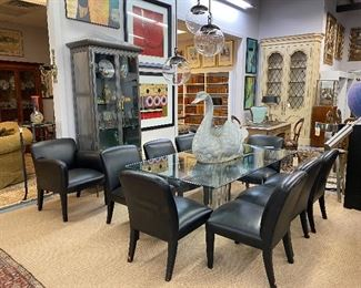 Set of eight Donghia black leather dining chairs.  Donghia leather Armchair  that surround a Karl Springer glass top dining table with Lucite supports.