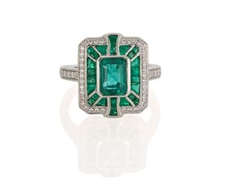 1005 An Emerald And Diamond Ring Platinum Centering a rectangular-cut emerald, gauged at approximately 1.25cts, and surrounded by twenty-seven baguette-cut emeralds, weighing approximately 0.95ct, and forty-eight round diamonds, totaling approximately 0.30ct. and graded G-H color and VS clarity Ring size: 8 8.85 grams Estimate: $2,500 - $3,500