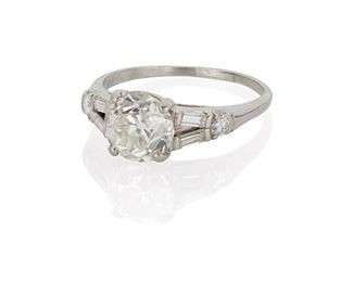 1010 An Art Deco Diamond Ring Platinum Centering an old European-cut diamond, gauged at 2.02cts and graded J-K color and VS clarity, flanked by two full-cut round and four baguette-cut diamonds, totaling approximately .3ct Ring size: 7.75 4.4 grams Estimate: $5,000 - $7,000