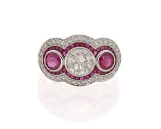 1012 A Ruby And Diamond Ring 18k white gold Centering a full-cut round diamond, weighing 1.26cts and graded M+ color and I clarity, flanked by two round rubies, totaling 1.02cts, and further set with calibre-cut rubies and full-cut round diamonds Ring size: 7.5 4 grams Estimate: $2,500 - $3,500