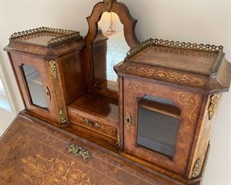 Slant Front Desk from 19th Century France with Center raised mirror flaked by compartments, Bronze Gallery and mounts, pigeonholed interior having four compartments with 3 drawers and leather writing area.  Bought from London and appraised at $8,000 in 2008. 60x100x18.