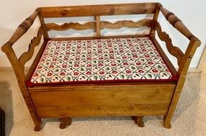 """This style of Swedish bench was formerly known as a """"maid's bed."""" This bench was originally designed as a type of """"spare bed,"""" as the lower section would pull out to reveal a small mattress inside and was typically kept in the kitchen, next to the table. The seat still lifts up (and off) to reveal storage below, as seen in the photos  This unique vintage wooden storage bench measures 27x29x40 inches. This bench has a beautiful needlepoint bench pad that accompanies it."""