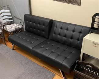 Modern futon.  Flattens down to a bed and then to a box for storage.