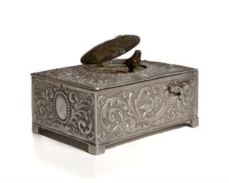 """1002 A German Silver Singing Bird Automaton Music Box Fourth-quarter 19th Century Marked to base with unidentified bird mark The rectangular-form bird-box with silver case chased with avian motifs and scrolling acanthus, the top centering an oval hinged lid with repousse putto revealing a reticulated grill with singing feathered automaton bird, with bird-form activation switch 1.875"""" H x 3.875"""" W x 2.875"""" D Estimate: $1,500 - $2,500"""