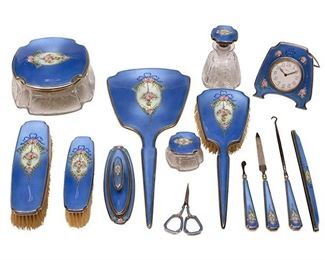 """1004 A Thomae Company Sterling Silver And Blue Guilloché Enamel Vanity Set Circa 1920s Most pieces marked for Thomae Company, sterling, and further numbered Each with light blue guilloche enamel centering pink floral bouquets with ribbons, comprising a hand mirror, three brushes, three powder jars, a nail buffer, a nail file, a cuticle pusher, scissors, a button hook, a clock, and the original handle for a comb, 14 pieces Largest: 13.25"""" L x 5.625"""" W; Smallest: 3.625"""" L x 2.125"""" W Estimate: $2,000 - $3,000"""