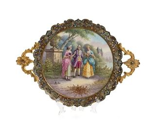 """1008 A French Gilt-Bronze And Champlevé Enamel Tazza Fourth-quarter 19th Century Signed illegibly to porcelain The circular tazza centering a painted porcelain plaque of courtiers in a landscape enclosed by a gilt-bronze border with polychrome champleve enamel flanked by two rocaille handles and raised on four feet 1.25"""" H x 13"""" W x 9.5"""" D Estimate: $800 - $1,200"""