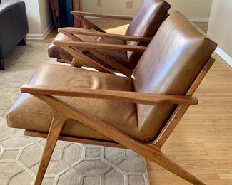 """Pair of Crate & Barrel Cavett Leather Chairs, wood frame in Sumatra.  Both chairs are in good overall condition with light wear to the leather; providing a distressed look. One chair has more wear than the other.   Measurements: arm to arm 25"""" and about 29.5"""" overall height."""