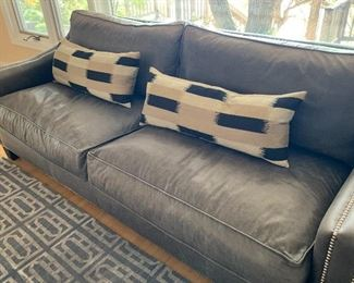 Custom made sofa by Kelsey Sofa. Color on original record notes navy leather.  However, the sofa appears to be a lovely neutral gray color. Some spots mainly the top of the cushions nearest the window are faded from the sunlight. Has nice brad detailing  Includes two decorative throw pillows.   Original purchase price of $4,000