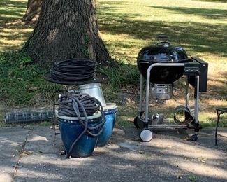 Weber performer charcoal grill, large planters, garden hoses, garden fencing.